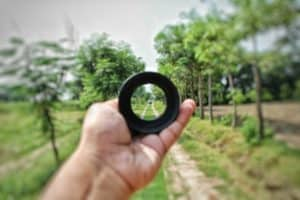 hand holding camera lense at arms lengths focusing on old country road