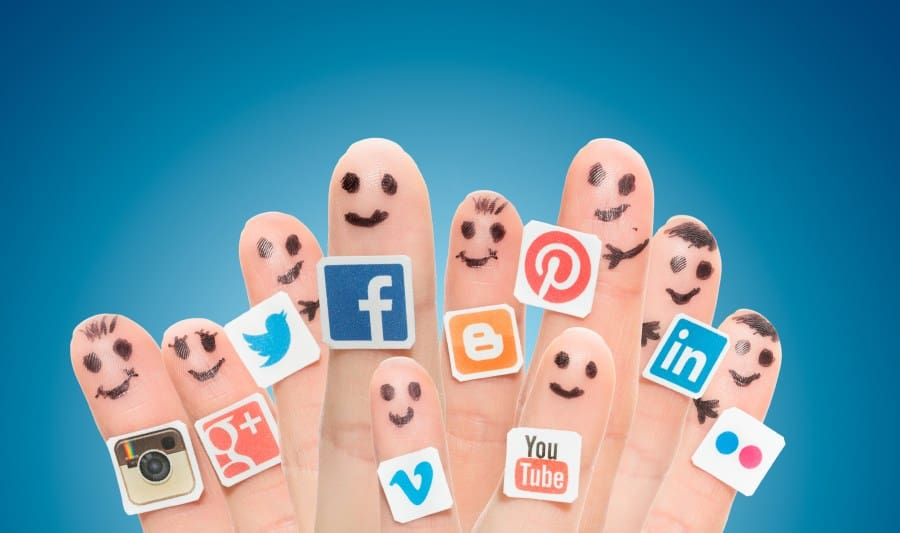many fingertips with smiley faces drawn on and various social media logo stickers placed on them