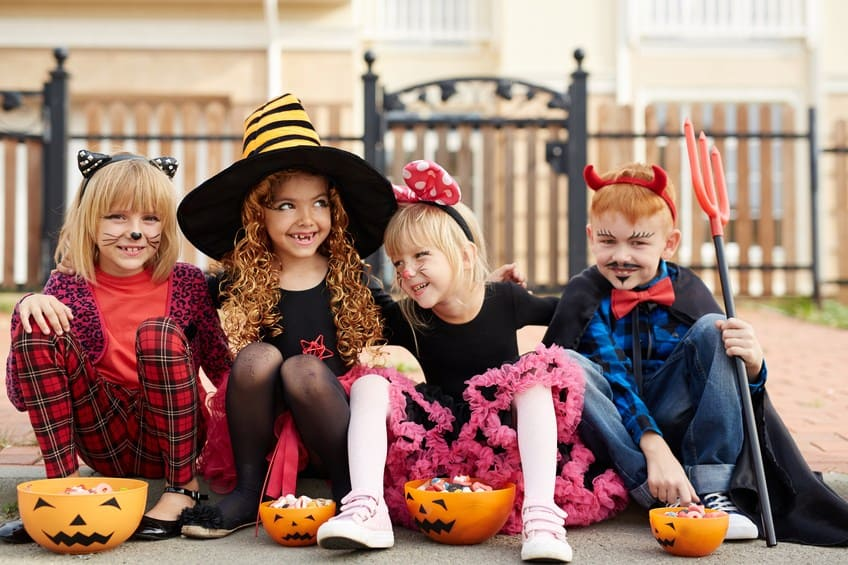 four young kids in various halloween costumes
