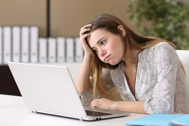 young lady looking frustrated at laptop
