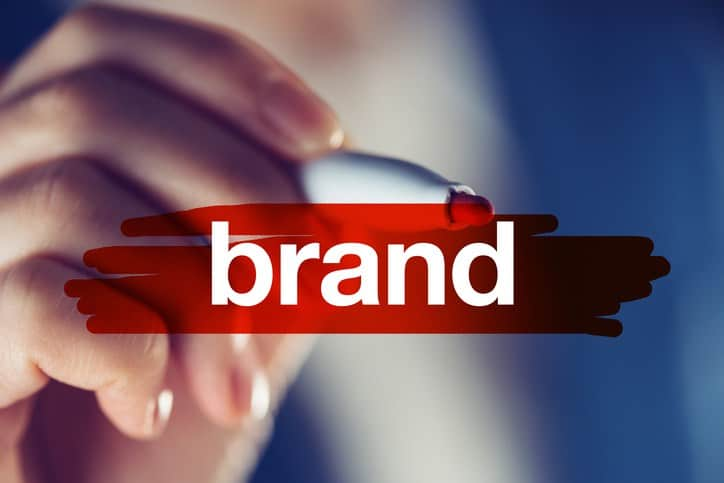 female hand highlighting the word brand