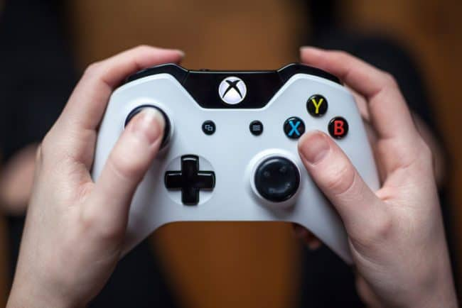 close up of two hands on xbox conroller