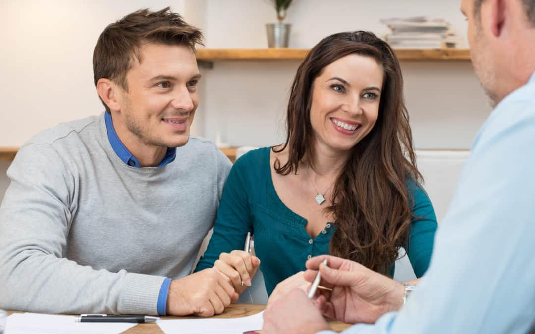 couple at bank smiling with loan officer