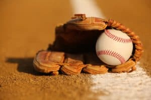close up of baseball glove holding baseball lying on chalk baseline
