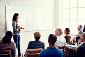photo of female speaker teaching a group of adults