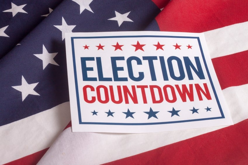 usa flag lying on table top with sign on top that says election countdown