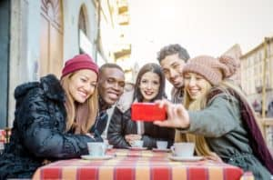 photo of five young adults taking selfie over coffee