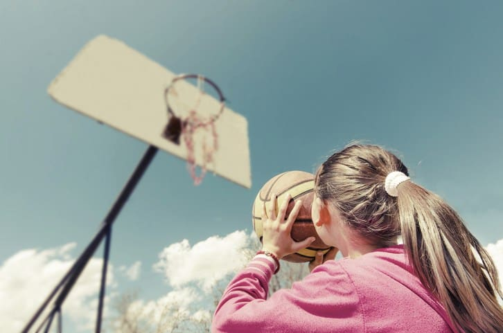 young girl aiming basketball at hoop with sky in background