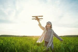 child with toy airplane running through a field
