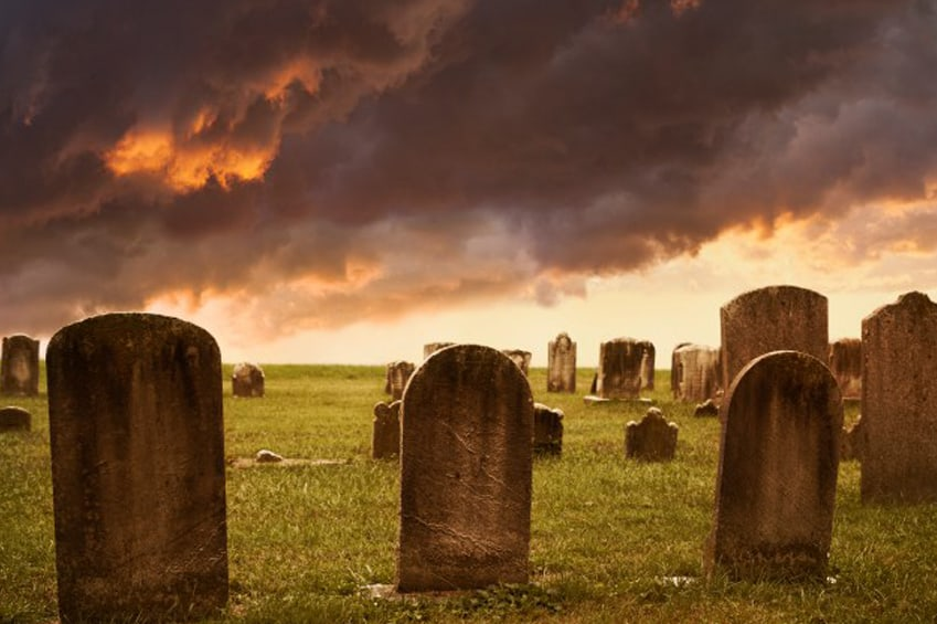 photo of an old cemetary with ominous clouds overhead