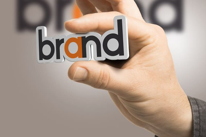 hand holding cardboard cut out of the word brand