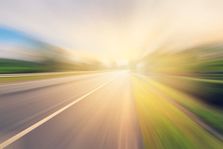 etheral photo of vehicle on street traveling so fast it is out of focus