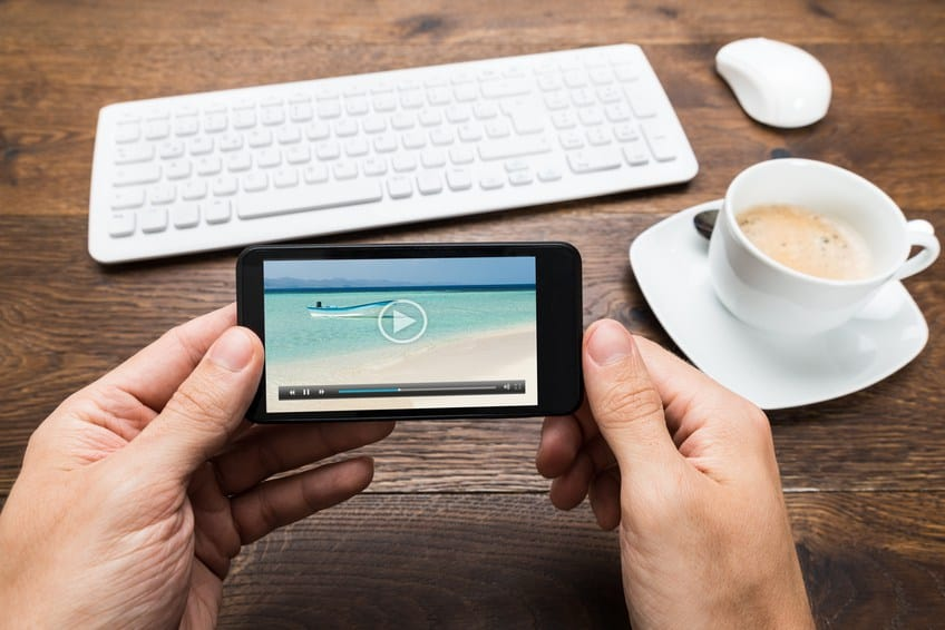 two hands holding smart phone horizontal to watch video