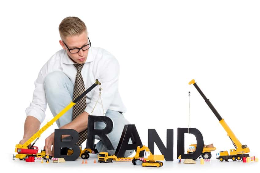 man trying to measure wooden letters that spell brand