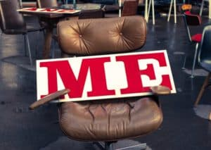 close up of a desk chair and giant poster that says ME lying in the seat